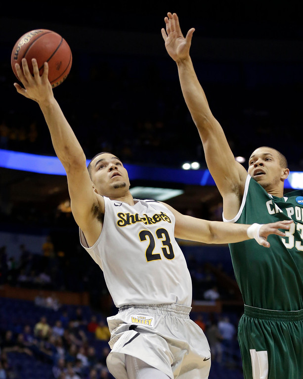 . Wichita State guard Fred VanVleet (23) shoots as Cal Poly forward Chris Eversley (33) defends during the first half of a second-round game in the NCAA college basketball tournament Friday, March 21, 2014, in St. Louis. (AP Photo/Charlie Riedel)
