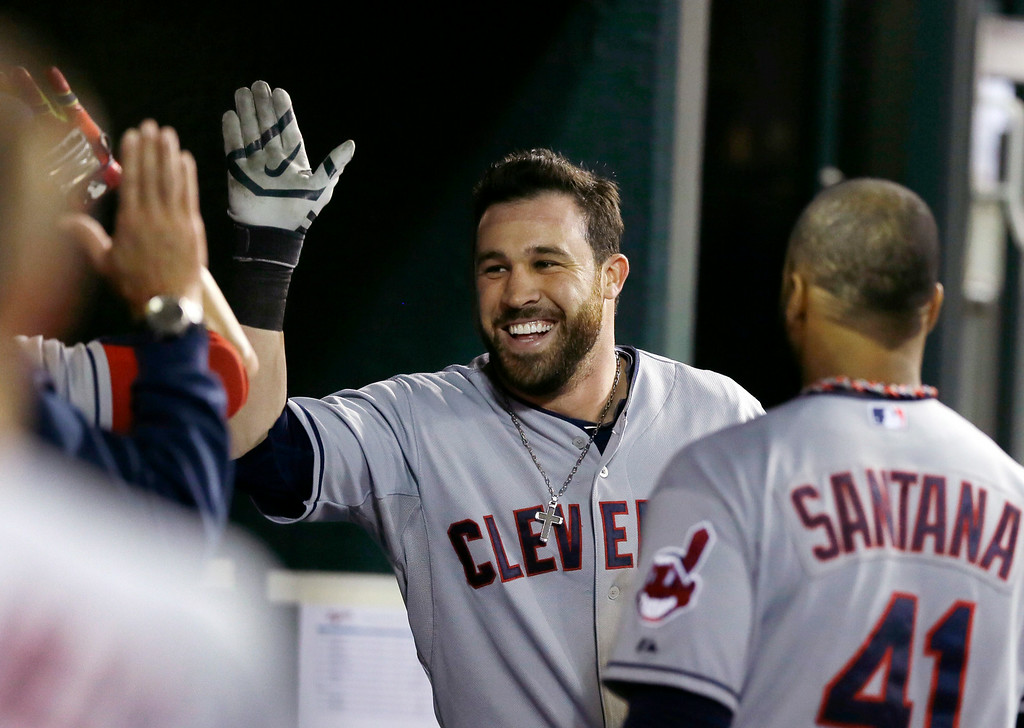 . Cleveland Indians\' Jason Kipnis is congratulated in the dugout after his solo home run off Detroit Tigers relief pitcher Chad Smith during the ninth inning of a baseball game in Detroit, Friday, July 18, 2014. (AP Photo/Carlos Osorio)
