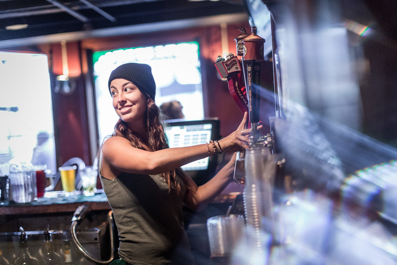A bartender girl pouring beer.