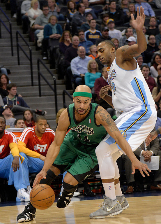 . Boston Celtics point guard Jerryd Bayless (11) drives around Denver Nuggets power forward Darrell Arthur (00) during the third quarter January 7, 2014 at Pepsi Center. (Photo by John Leyba/The Denver Post)