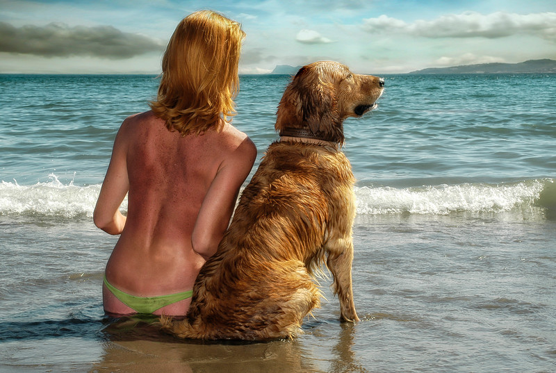 Woman and her dog on a beach in the Costa Del Sol, Andalucia, Spain.