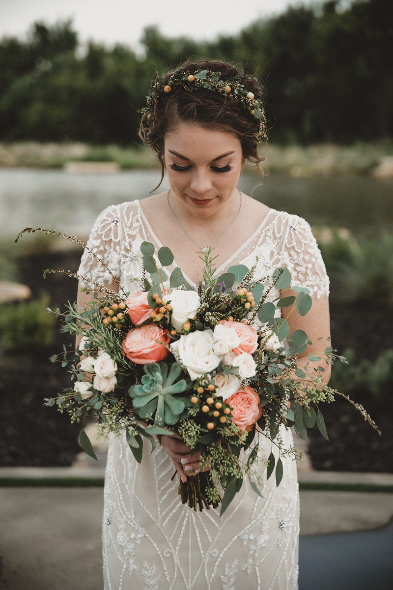bride looking down at her large bouquet of choral green and white flowers