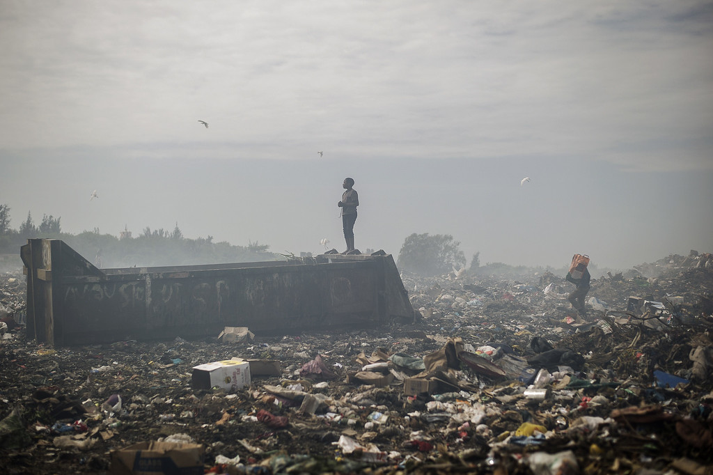 . A boy stands at the Maputo municipal garbage dumping site as others sift through garbage in Maputo on October 14, 2014. GIANLUIGI GUERCIA/AFP/Getty Images