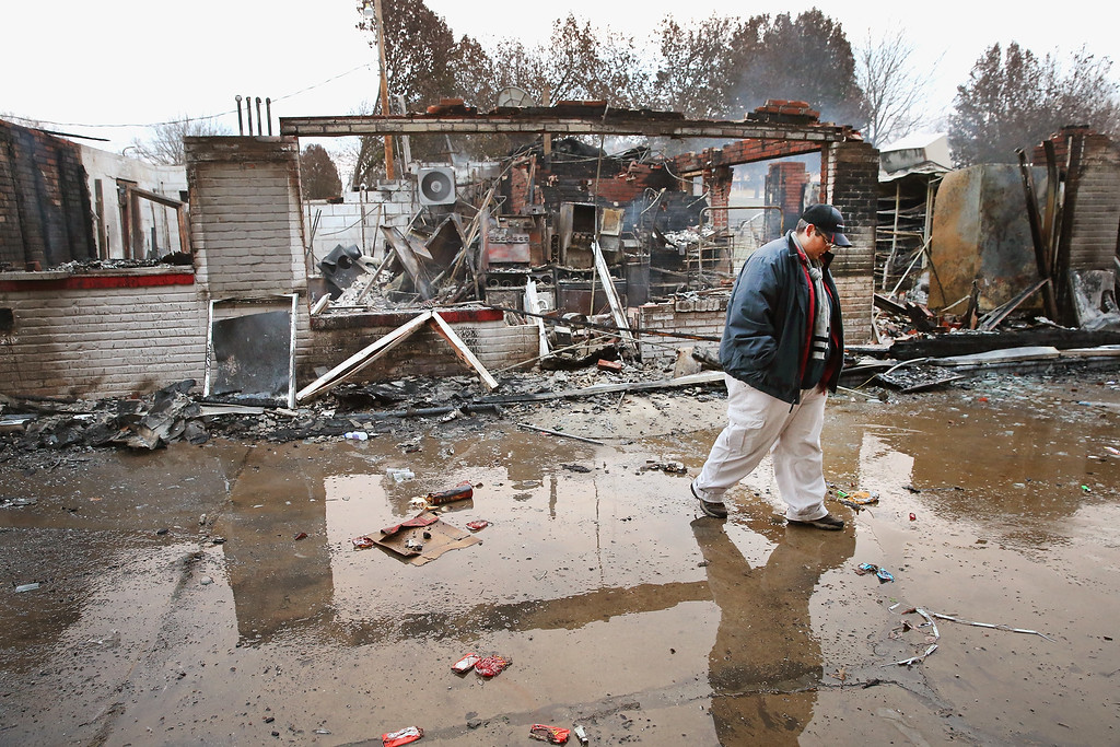 . Property manager Terri Willits looks over a gas station she manages that was set on fire when rioting erupted following the grand jury announcement in the Michael Brown case on November 25, 2014 in Dellword Missouri. Brown, an 18-year-old black man, was killed by Darren Wilson, a white Ferguson police officer, on August 9. At least 12 buildings were torched and more than 50 people were arrested during the night-long rioting.  (Photo by Scott Olson/Getty Images)