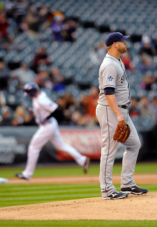 . San Diego Padres starting pitcher Eric Stults looks away as Colorado Rockies\' Drew Stubbs rounds the bases after Stubbs hit a solo home run in the first inning of a baseball game Friday, Sept. 5, 2014, in Denver. (AP Photo/Chris Schneider)