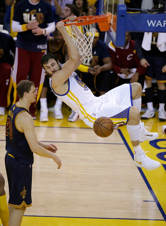 . Golden State Warriors center Andrew Bogut, right, dunks against Cleveland Cavaliers center Timofey Mozgov during the second half of Game 1 of basketball\'s NBA Finals in Oakland, Calif., Thursday, June 4, 2015. (AP Photo/Eric Risberg)