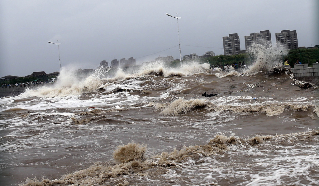 """. This picture taken on August 22, 2013 shows huge waves from the \""""Haining tide\"""" - a daily occurrence when the river tides hit the banks of the city - surging higher than usual due to the influence of Typhoon Trami in the region in Haining, in eastern China\'s Zhejiang province. Typhoon Trami, the 12th typhoon to hit China this year, brought rainstorms and wreaked havoc in eastern China after landing in Fujian Province early on August 22.  The tides there have attracted spectators for the past two millennia, and it is the scene of an annual Tide-Watching Festival in late summer.     AFP PHOTOSTR/AFP/Getty Images"""