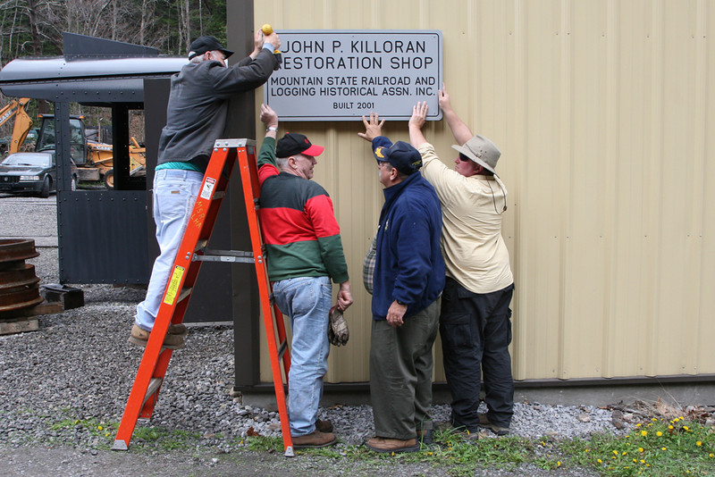 Volunteers attach a new sign to the MSRLHA restoration shop. April 2007