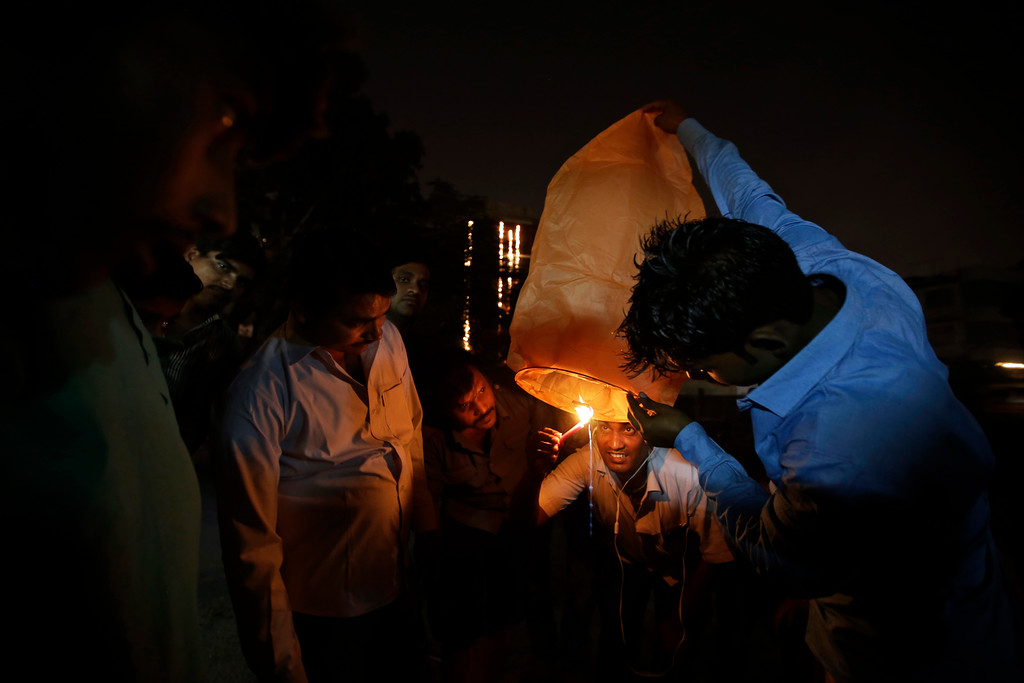 . An Indian lights a sky lantern during Diwali festival in New Delhi, India, Thursday, Oct. 19, 2017. The Supreme Court this year banned the sale of firecrackers in the Indian capital and neighboring areas to prevent a toxic haze after the Diwali nights that has residents hiding indoors. (AP Photo/Altaf Qadri)