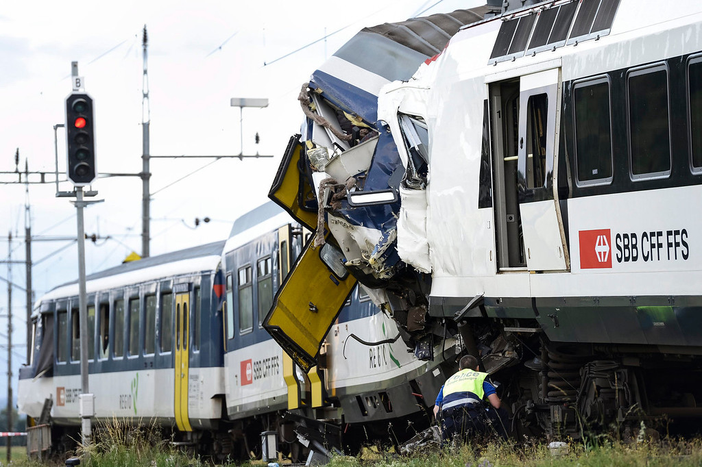 . A signal shows red light as a police officer works at the site where two passenger trains collided head-on in Granges-pres-Marnand, western Switzerland, Monday, July 29, 2013. Police says that 44 people have been injured.  (AP Photo/Keystone, Laurent Gillieron)