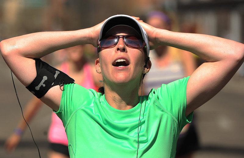 . Sierra Lund puts her hands on her head after finishing the 5 mile race.  The 31st annual Cherry Creek Sneak had all sorts of distances for this year\'s race.  The Sneak, as it is affectionately named, had a 10 mile, 5 mile, 3.1 mile or 5K, a 1.5 mile Denver\'s 7 Sprint, and a kid\'s fun run for thousands of competitors, runners and walkers that turned out in the Cherry Creek neighborhood of Denver, CO on April 28, 2013.  The race is always held the last Sunday in April. This year participants cheered the national anthem and observed a moment of silence for victims of the Boston Marathon bombing at the start of each race. (Photo by Helen H. Richardson/The Denver Post)