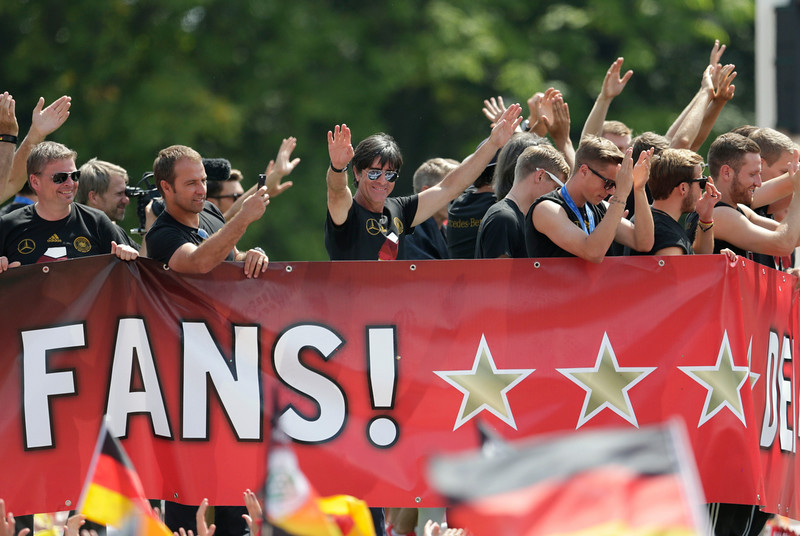 . Germany\'s head coach Joachim Loew, center, waves to the supporters during a fan party after the arrival of the German national soccer team in Berlin Tuesday, July 15, 2014. Germany beat Argentina 1-0 on Sunday to win its fourth World Cup title.  (AP Photo/Petr David Josek)