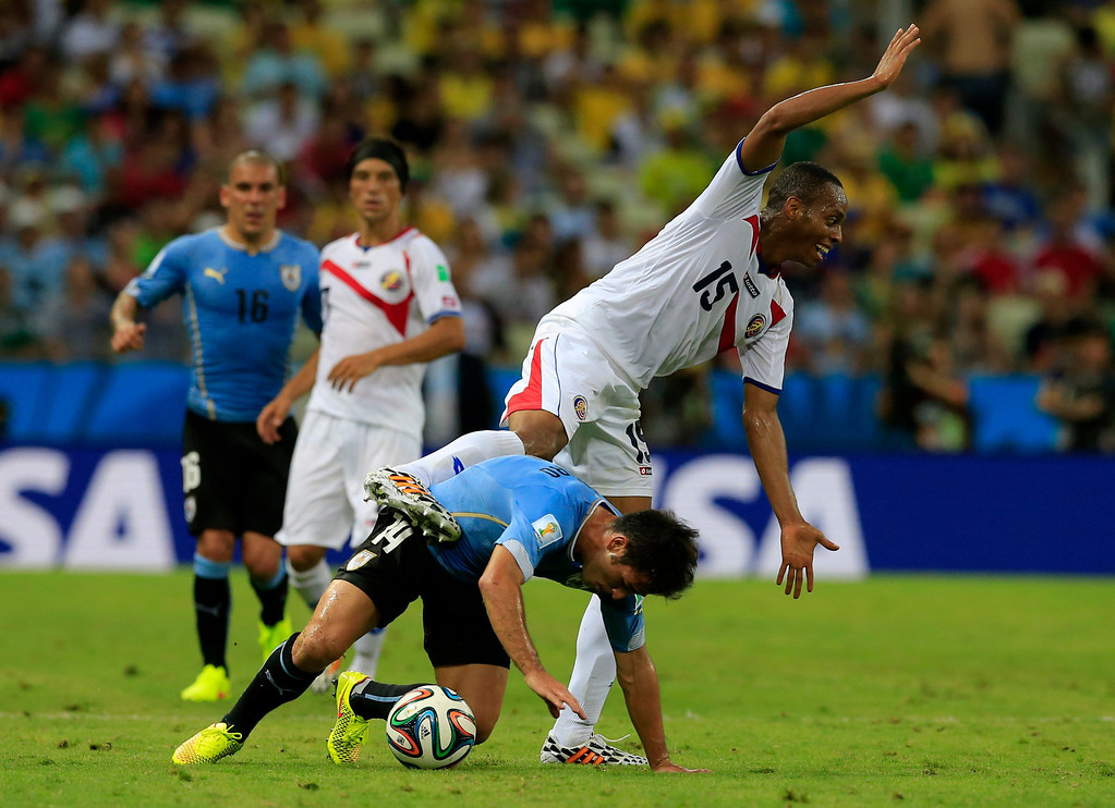 . Costa Rica\'s Junior Diaz, rear, challenges Uruguay\'s Nicolas Lodeiro during the group D World Cup soccer match between Uruguay and Costa Rica at the Arena Castelao in Fortaleza, Brazil, Saturday, June 14, 2014.  (AP Photo/Bernat Armangue)