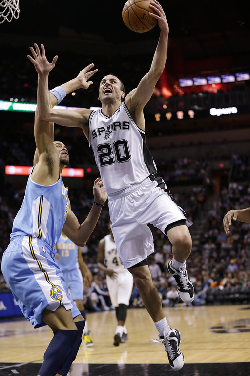 . San Antonio Spurs\' Manu Ginobili (20), of Argentina, drives to the basket past Denver Nuggets\' JaVale McGee, left, during the first half of an NBA basketball game, Wednesday, March 27, 2013, in San Antonio. (AP Photo/Eric Gay)