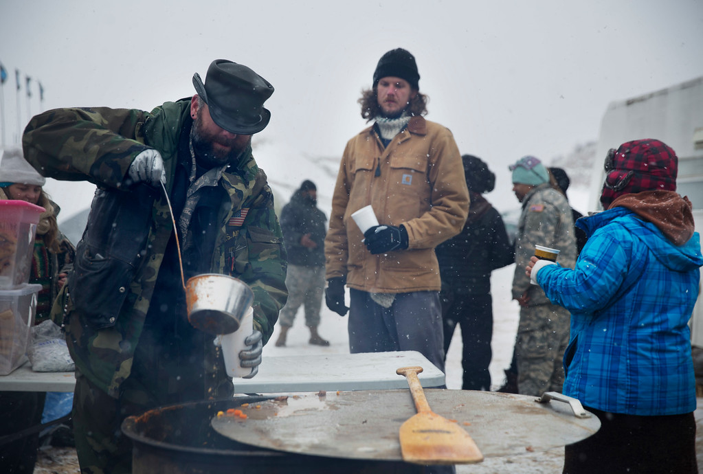 . U.S. Air Force veteran Jarrod Phillips, of St. Louis, left, serves stew to veterans at the Oceti Sakowin camp where people have gathered to protest the Dakota Access oil pipeline in Cannon Ball, N.D., Monday, Dec. 5, 2016. Many Dakota Access oil pipeline opponents who\'ve gathered for months in a camp in southern North Dakota are committed to staying despite wintry weather and demands that they leave. (AP Photo/David Goldman)