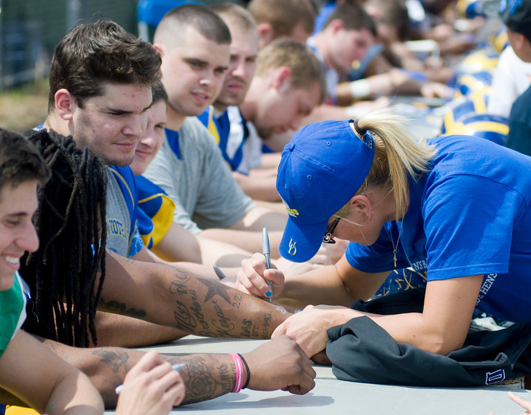 Who's the celebrity here?  Football players ask Kayla Miller of the Women's Basketball team to sign their arms