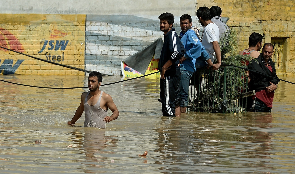 . Kashmiri people make their way through the floodwaters in Srinagar on September 10, 2014.    AFP PHOTO/ PUNIT  PARANJPE/AFP/Getty Images