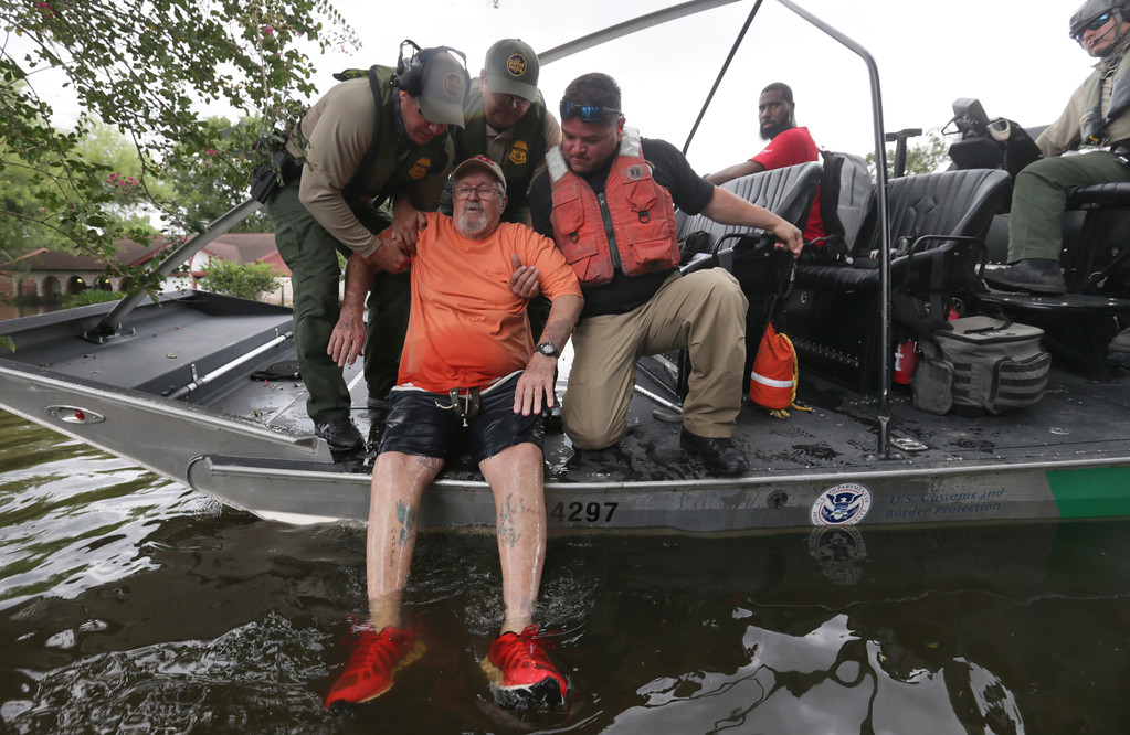 . John Paul Klotz, 80, is pulled on a boat by U.S. Border Patrol Agents Steven Blackburn, left, Ramiro Rodriguez, top center, and Juan Flores during a search a rescue operation in a neighborhood inundated by floodwaters from Tropical Storm Harvey in Houston, Texas, Wednesday, Aug. 30, 2017. (AP Photo/LM Otero)