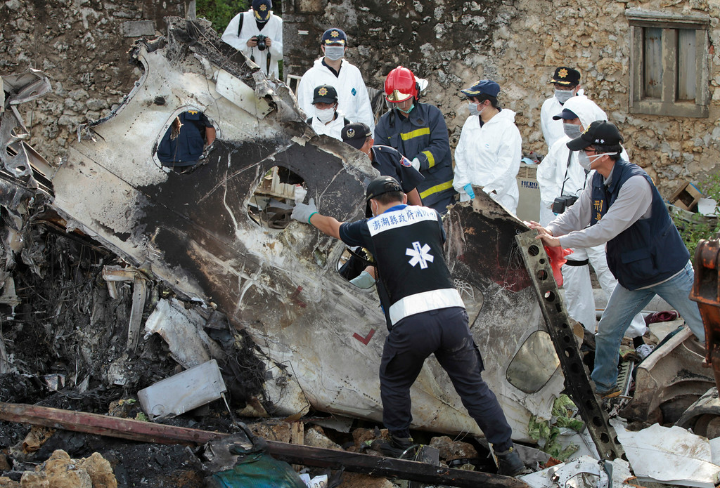 . A forensic team recovers human remains among the wreckage of crashed TransAsia Airways flight GE222 on the outlying island of Penghu, Taiwan, Thursday, July 24, 2014.  (AP Photo/Wally Santana)