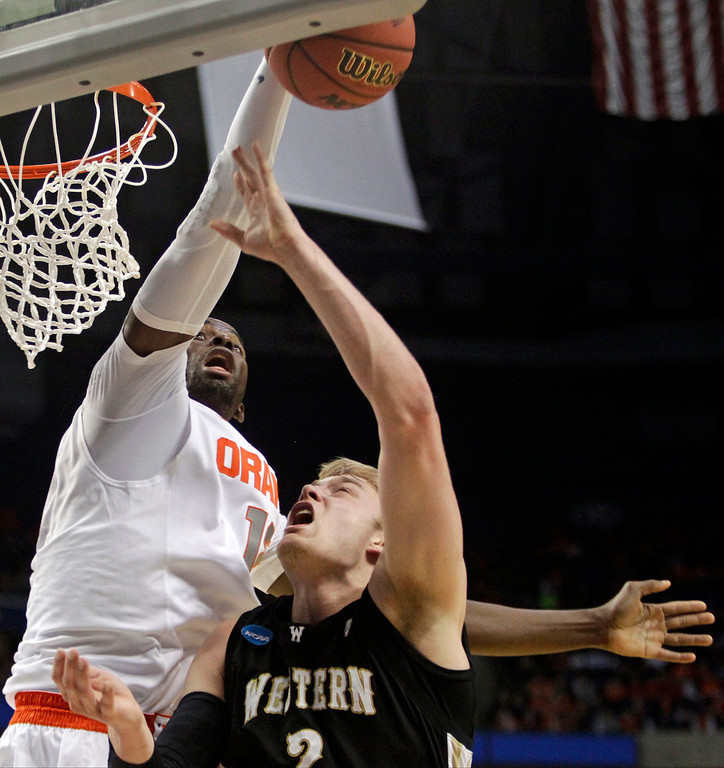. Syracuse\'s Baye-Moussa Keita, left, blocks a shot by Western Michigan\'s Connar Tava during the second half of a second-round game in the NCAA college basketball tournament in Buffalo, N.Y., Thursday, March 20, 2014. (AP Photo/Bill Wippert)