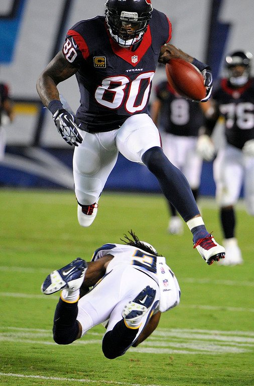 . Houston Texans wide receiver Andre Johnson leaps over San Diego Chargers defensive back Richard Marshall during the first half of an NFL football game Monday, Sept. 9, 2013, in San Diego. (AP Photo/Denis Poroy)