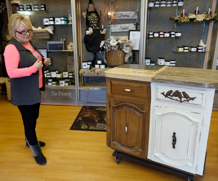 Kathy Campbell with a small display of cabinetry that has been painted with Plaster Paint.