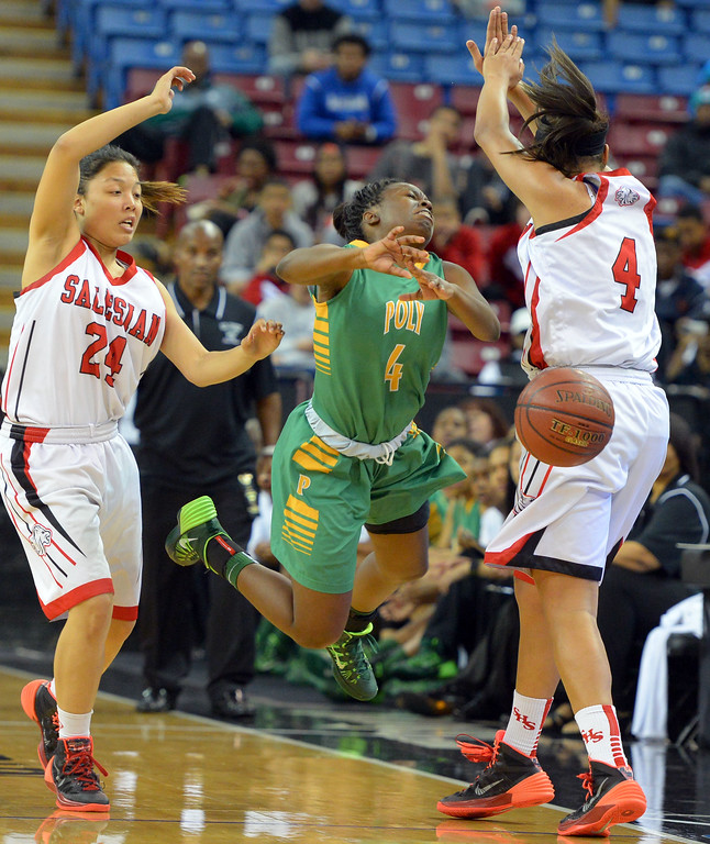 . Poly\'s Tania Lamb turns the ball over as she flies through the air between Salesian\'s Taylor Crowder, left, and Mariya Moore at Sleep Train Arena in Sacramento, CA on Saturday, March 29, 2014. Long Beach Poly vs Salesian in the CIF Open Div girls basketball state final. 1st half. (Photo by Scott Varley, Daily Breeze)