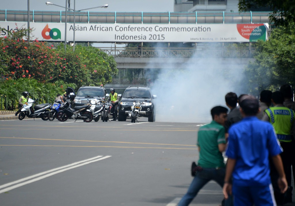 . Police (L) hide behind vehicles during an exchange of gunfire with suspects hiding near a Starbucks cafe when another blast happens in Jakarta on January 14, 2016. A series of bombs killed at least three people in the Indonesian capital Jakarta on January 14, with shots fired outside a cafe as police moved in, an AFP journalist at the scene said.     AFP PHOTO / Bay ISMOYOBAY ISMOYO/AFP/Getty Images
