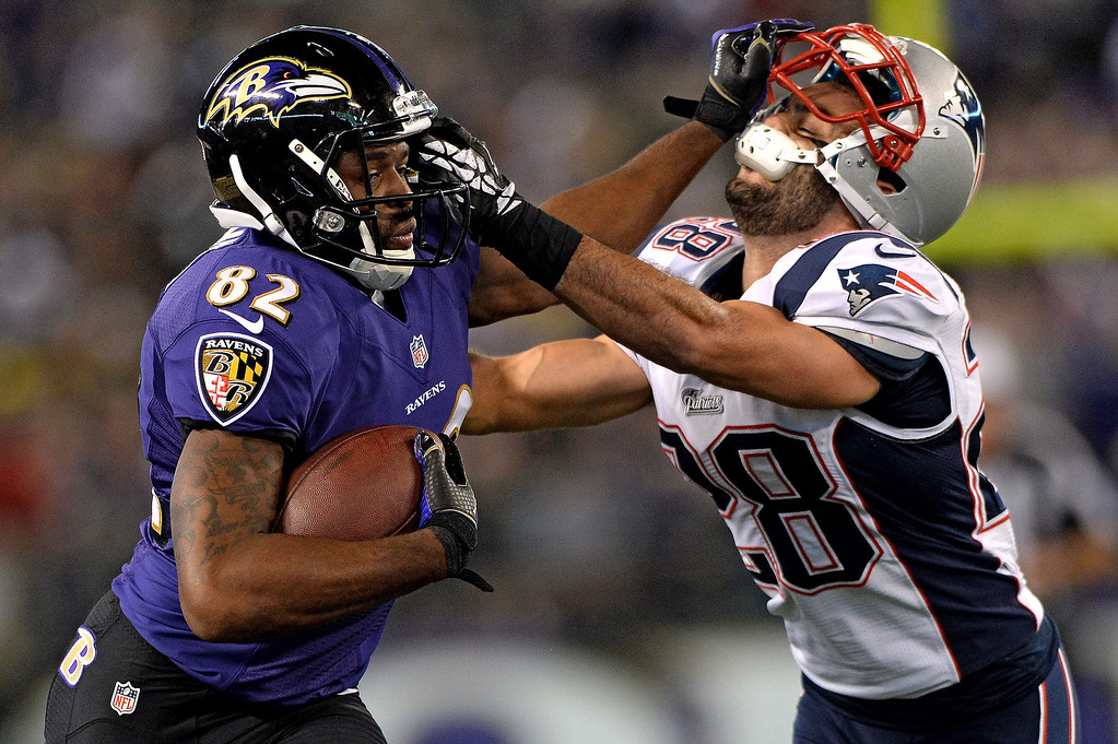 . Wide receiver Torrey Smith #82 of the Baltimore Ravens eludes strong safety Steve Gregory #28 of the New England Patriots in the third quarter at M&T Bank Stadium on December 22, 2013 in Baltimore, Maryland. The New England Patriots won, 41-7. (Photo by Patrick Smith/Getty Images)