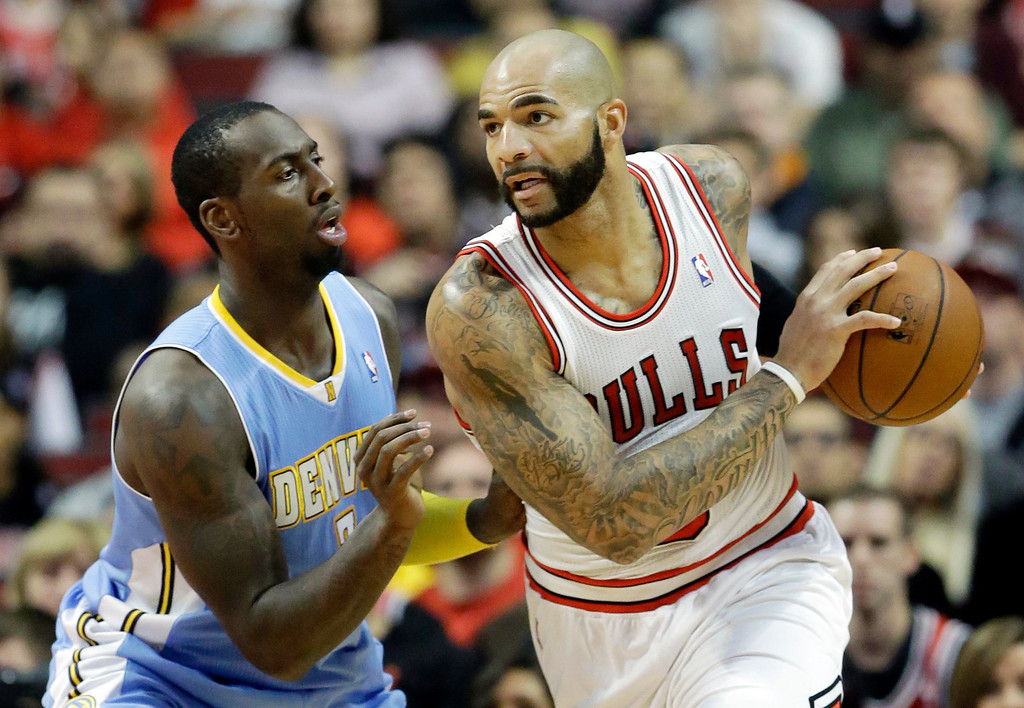 . Chicago Bulls forward Carlos Boozer, right, looks to pass as Denver Nuggets forward JJ Hickson (7) defends during the first half of an NBA preseason basketball game in Chicago on Friday, Oct. 25, 2013. (AP Photo/Nam Y. Huh)