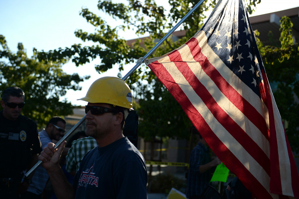 . Construction worker Paul Hathaway, of Murrieta, holds an american flag outside a town hall meeting on Wednesday, July 2, 2014 at Murrieta Mesa High School in Murrieta, Ca. The meeting is being held in response to immigrants who were being processed through a Texas Border Patrol Station and delivered to the Murrieta Border Patrol Station on Tuesday, which created protests from both sides of the immigration issue. (Micah Escamilla/The Sun)