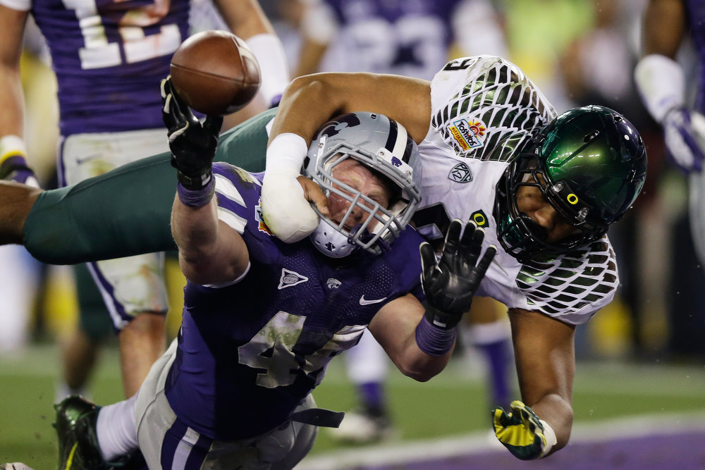 Description of . Byron Marshall #9 of the Oregon Ducks tackles Ryan Mueller #44 of the Kansas State Wildcats in the endzone on a blocked extra point attempt that resulted in a safety during the Tostitos Fiesta Bowl at University of Phoenix Stadium on January 3, 2013 in Glendale, Arizona.  (Photo by Ezra Shaw/Getty Images)