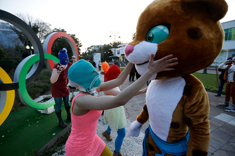 . Pussy Riot member Nadezhda Tolokonnikova in the aqua balaclava, left, interacts with an Olympic mascot while the group perform next to the Olympic rings in Sochi, Russia, on Wednesday, Feb. 19, 2014. Cossack militia attacked the punk group with horsewhips earlier in the day as the artists - who have feuded with Vladmir Putin\'s government for years - tried to perform under a sign advertising the Sochi Olympics. (AP Photo/David Goldman)