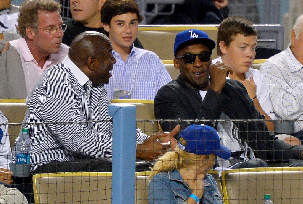 ". Los Angeles Dodgers co-owner and former Los Angeles Laker Earvin ""Magic\"" Johnson, left, talks with Los Angeles Lakers\' Kobe Bryant as they watch the Dodgers play the New York Yankees in a baseball game, Wednesday, July 31, 2013, in Los Angeles. (AP Photo/Mark J. Terrill)"
