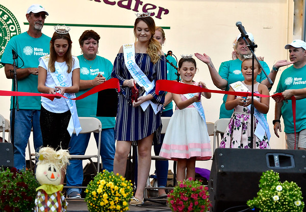 9/20/2018 Mike Orazzi | Staff Junior Miss Mum Carson Gagne, Miss Mum Kayla Paulette, Petite Miss Mum is Leah Aparo and Mini Miss Mum Gianna Cassin cut the ribbon to kick off this year's mum festival on Memorial Blvd. Thursday evening.