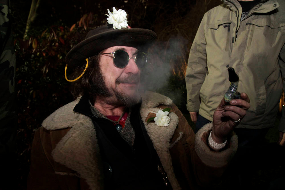 ". A man known as ""Professor Gizmo,\"" smokes marijuana in a glass pipe, Wednesday, Dec. 5, 2012, just before midnight at the Space Needle in Seattle. Possession of marijuana became legal in Washington state at midnight, and several hundred people gathered at the Space Needle to smoke and celebrate the occasion, even though the new law does prohibit public use of marijuana. (AP Photo/Ted S. Warren)"