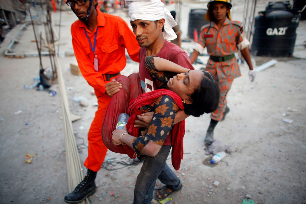 . Rescue workers carry a garment worker who was trapped in the Rana Plaza building which collapsed, in Savar, 30 km (19 miles) outside Dhaka April 24, 2013. REUTERS/Andrew Biraj