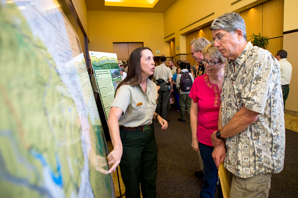 . Wildlife biologist Ann Berkley, of the U. S. Forest Service, speaks with Colleen and Brian Bennett, of La Verne, during a San Gabriel Mountains meeting Tuesday night, August 26, 2014 at Baldwin Park Performing Arts Center. Rep. Judy Chu has a bill to make the area a national recreation area but has since asked President Obama to make the mountains a national monument.  Brian is with the La Verne Land Conservancy. (Photo by Sarah Reingewirtz/Pasadena Star-News)