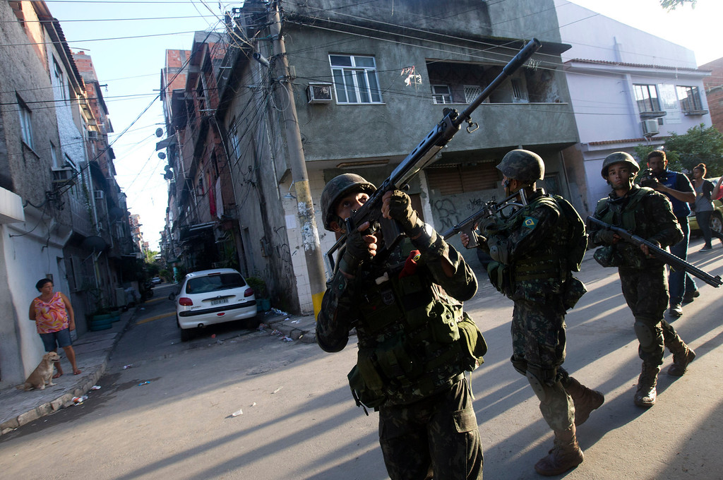 . Army soldiers take position during an operation to occupy the Mare slum complex in Rio de Janeiro, Brazil, Saturday, April 5, 2014. More than 2,000 Brazilian Army soldiers moved into the Mare slum complex early Saturday in a bid to improve security and drive out the heavily armed drug gangs that have ruled the sprawling slum for decades. (AP Photo/Silvia Izquierdo)