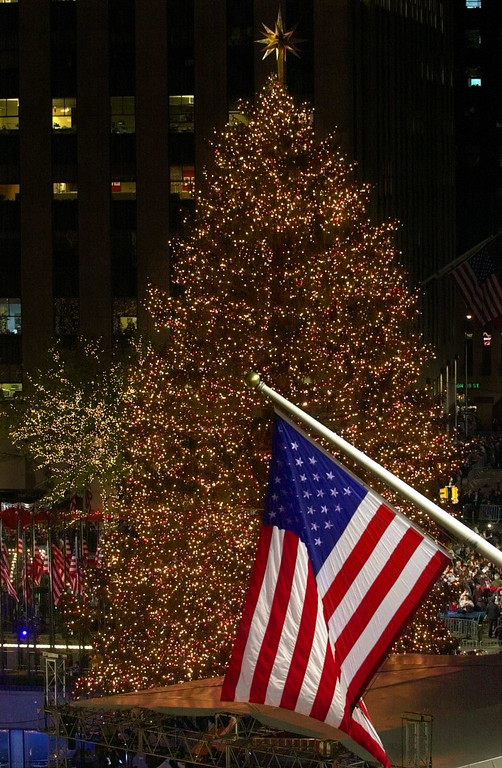 . An American Flag flies in front of the annual Rockefeller Center Christmas tree following the lighting ceremony, Wednesday, Nov. 28, 2001, in New York. (AP Photo/Suzanne Plunkett)