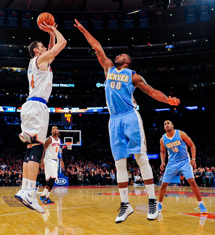 . NEW YORK, NY - NOVEMBER 16: Jason Smith #14 of the New York Knicks shoots over Darrell Arthur #00 of the Denver Nuggets in the second half at Madison Square Garden on November 16, 2014 in New York City. NOTE TO USER: User expressly acknowledges and agrees that, by downloading and/or using this photograph, user is consenting to the terms and conditions of the Getty Images License Agreement.  (Photo by Alex Goodlett/Getty Images)