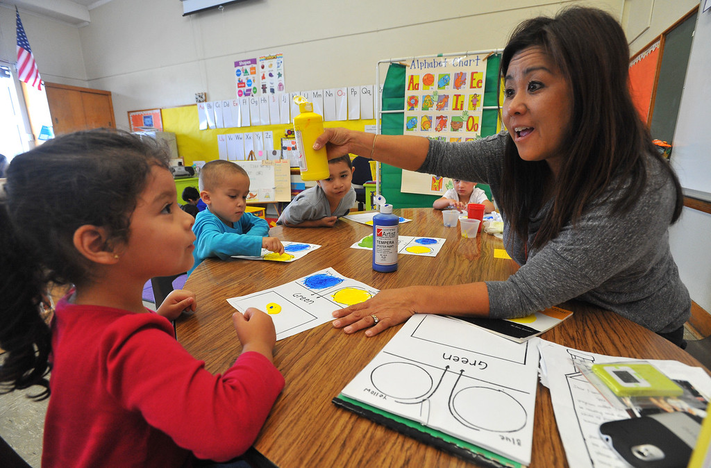 . Pre-school teacher Aimee Iwasaki works with her mild to moderately disabled students including Aimee Hernandez, left, on a painting and colors exercise at Buffum Total Learning Center in Long Beach, CA on Wednesday, October 9, 2013.  Beginning next week, Buffum, a pre-school for special needs students, will start a program called Typical Peers which will have their students with disabilities working side by side with normally developing students. (Photo by Scott Varley, Daily Breeze)