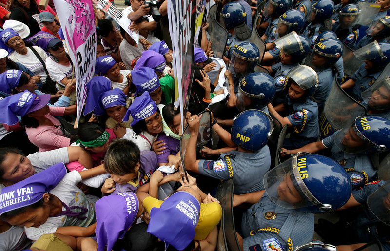 . Filipino protesters clash with police as the former try to march closer to the US Embassy in Manila to commemorate International Women\'s Day Friday March 8, 2013 in the Philippines. Thousands of Filipinos commemorate Women\'s Day with calls to stop violence against women and children. (AP Photo/Bullit Marquez)