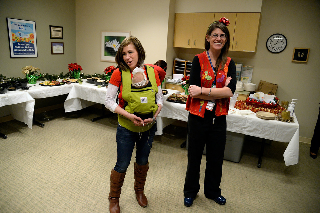 . AURORA, CO - DECEMBER 25: Nurse Sarah Hodgin stands with Jessica Lohmeyer as she holds her daughter, Heather, who was born with a chromosome disorder and had to spend her early life in the NICU. Lohmeyer along with her husband, Thomas, helped organize a staff meal for nurses and other hospital staff work on Christmas day at Children\'s Hospital on Wednesday, December 25, 2013. (Photo by AAron Ontiveroz/The Denver Post)