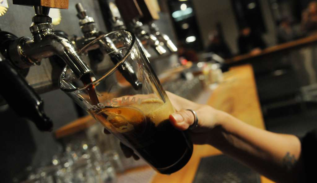 . Bartender Missi Sommers-Bachman pours a glass of Dangerous Man\'s chocolate milk stout. (Pioneer Press: John Autey)