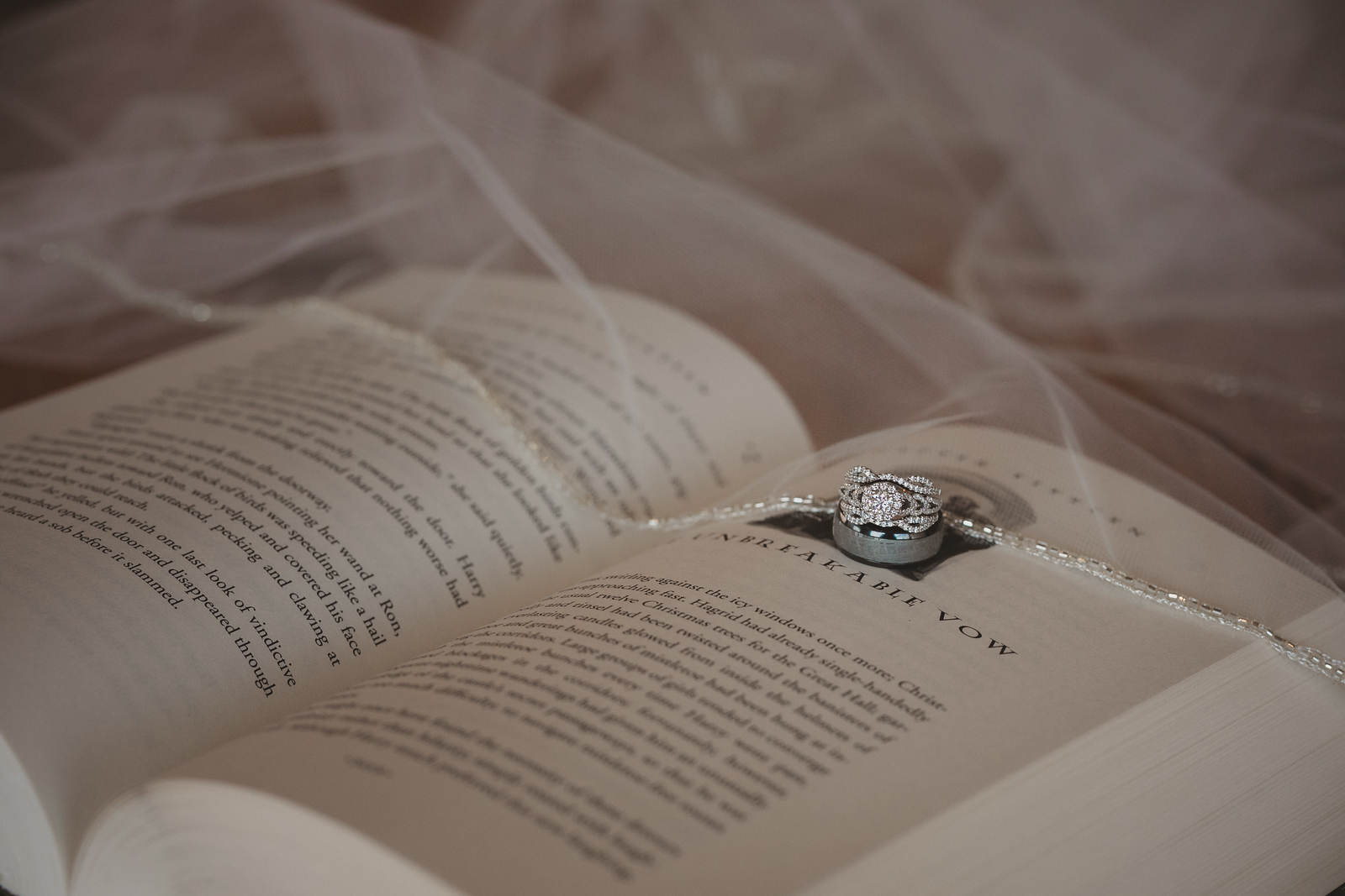 wedding rings and bracelet sitting on an open harry potter book atop a brides wedding vail