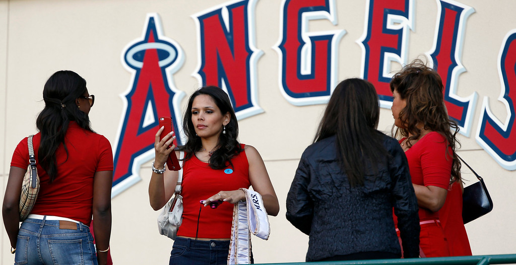 . Mrs. Globe 2013, Sheryl Ann Baas, second from left, of Holland, takes a photo of Ivy Heward-Mills of Ghana, a competitor for the October competition, as they arrive at at Angel Stadium to see their first baseball game between the Seattle Mariners and Los Angeles Angels Tuesday, May 21, 2013 in Anaheim.    (AP Photo/Alex Gallardo)