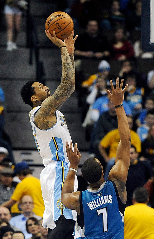 . Denver Nuggets guard Wilson Chandler, left, shoots over Minnesota Timberwolves forward Derrick Williams (7) in the first quarter of an NBA basketball game on Saturday, March 9, 2013, in Denver. (AP Photo/Chris Schneider)