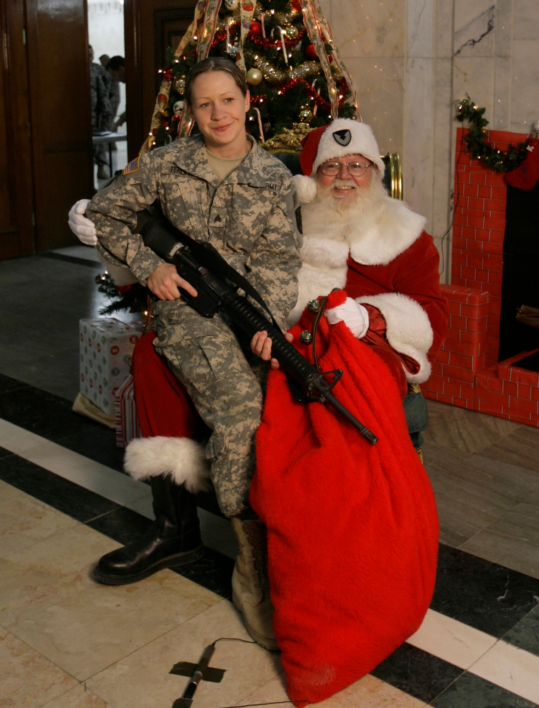 Description of . A US soldier  poses as she sits on a lap of man dressed as Santa Claus at al-Faw palace at Camp Victory at the airport in Baghdad, Iraq, Monday, Dec. 15, 2008.  (AP Photo/Khalid Mohammed)