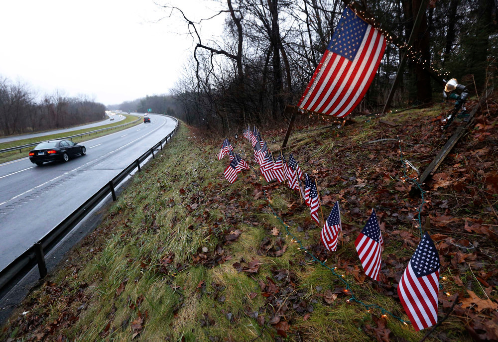Description of . Twenty-seven small U.S. flags adorn a large flag on a makeshift memorial on the side of Highway 84 near the Newtown, Conn., town line as residents mourn victims killed by gunman Adam Lanza, Monday, Dec. 17, 2012. Authorities say Lanza killed his mother at their home and then opened fire inside the Sandy Hook Elementary School in Newtown, killing 26 people, including 20 children, before taking his own life, on Friday. (AP Photo/Julio Cortez)